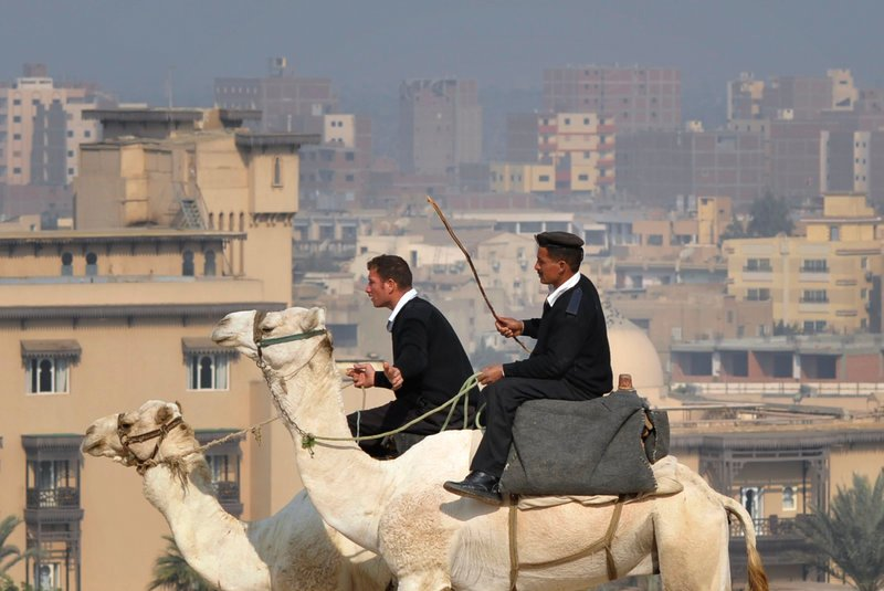 Egyptian policemen patrol on camels close to the Giza Pyramids near Cairo, Egypt, on Saturday. The vote for parliament's lower house is taking place over three stages, with 18 provinces in Egypt yet to vote.