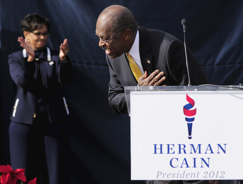Republican presidential candidate Herman Cain bows and his wife, Gloria, applauds as Cain arrives on stage for his announcement Saturday in Atlanta, at what was to have been the opening of his national campaign headquarters.