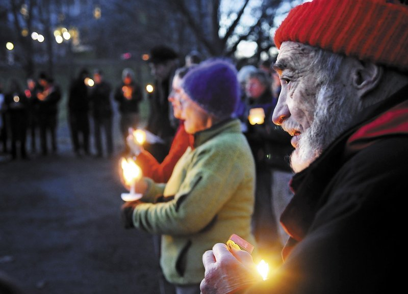 Charles Acker of Whitefield holds a candle Sunday during a vigil with members of several local church congregations to show solidarity with the Occupy Augusta members at Capitol Park in Augusta.