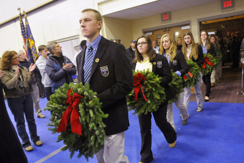 Cheverus students, from left, Spencer Amberson, Michelle Giordano and Aliza Hellier lead a procession into the gym during the Wreaths Across America salute.