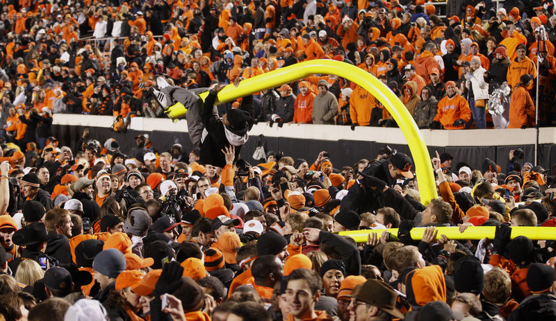 A fan hangs from a goal post after Oklahoma State's 44-10 football win over the University of Oklahoma in Stillwater, Okla., on Saturday, as thousands of fans flooded the field.