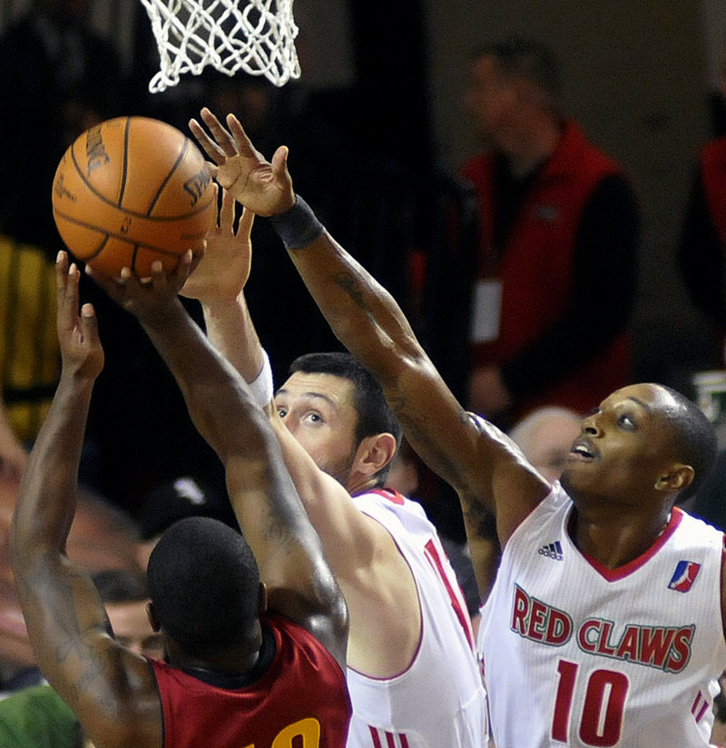 Mike Tisdale, center, and Kenny Hayes attempt to block Tory Jackson's shot in Sunday's game at Portland. The Red Claws rallied for a 99-91 win.
