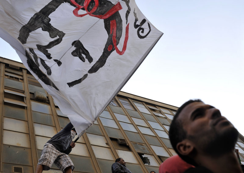 A protester waves a flag depicting Khaled Said, whose death at the hands of police in the city of Alexandria helped spark the uprising that ousted President Hosni Mubarak, at a rally in Cairo on Friday against Egypt's ruling military.