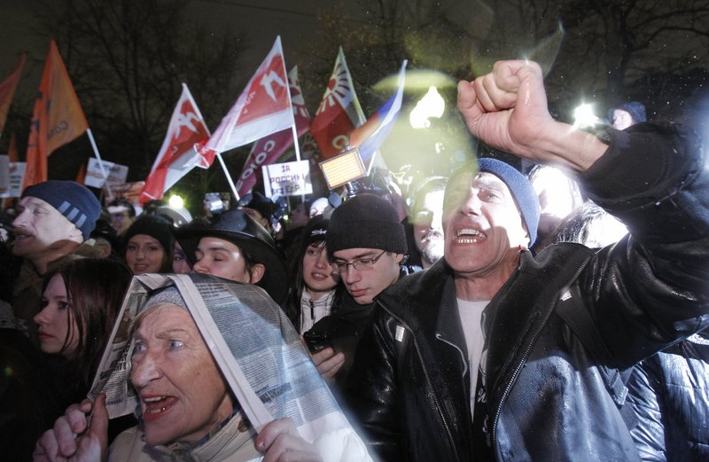 Members of the Russian opposition chant anti-goverment slogans during a rally in Moscow on Monday to protested against Prime Minister Vladimir Putin and his party.