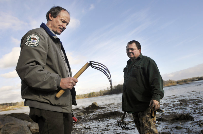 Andy Hutchinson of Saco, left, a park manager and naturalist at Wolfe's Neck Woods State Park, talks with Sanford Metayer of Lewiston about clam-digging implements during a demonstration at the park last Sunday.