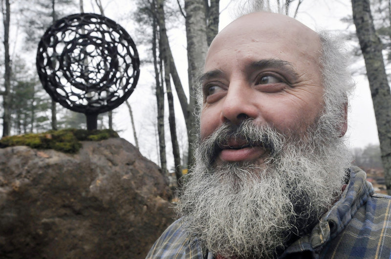 "Jay Sawyer suspended a spheroid created by Dave McLaughlin inside one of his own making for ""Late Collaboration,"" which stands in a sculpture garden on Sawyer's property in Warren. Sawyer vows to carry forward McLaughlin's vision for heavy-metal art."