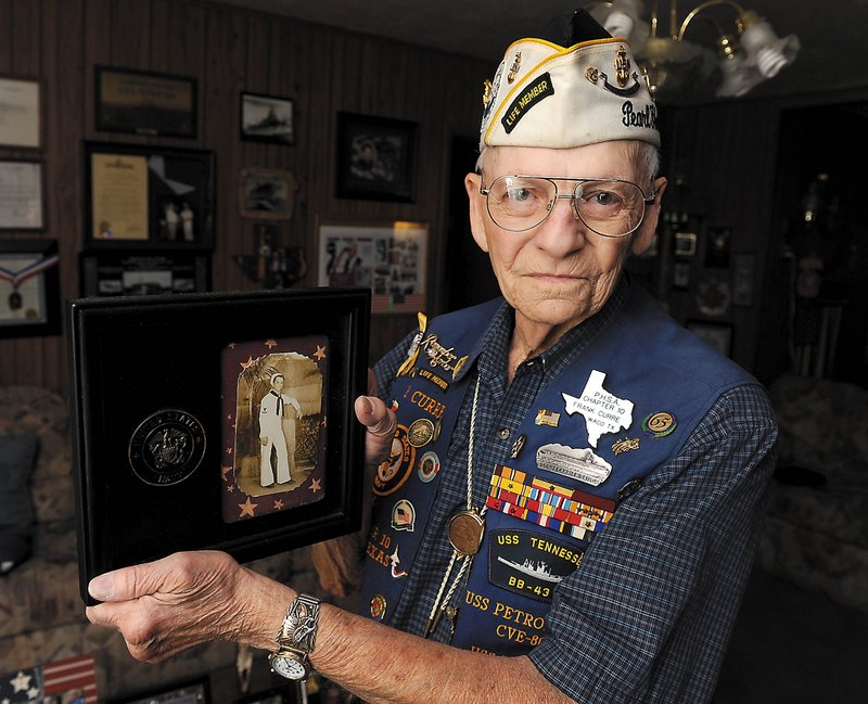Pearl Harbor veteran Frank Curre holds a photograph of himself as a young Navy sailor in this June 23, 2011, file photo in Waco, Texas. Curre died Wednesday, exactly 70 years after surviving the surprise Japanese attack on Pearl Harbor. The Waco native was 88 years old.