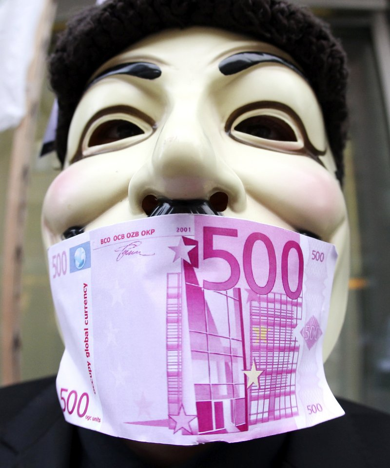 "A Frankfurt Occupy activist wears an ""occupy global currency"" bill on his mask in front of the European Central Bank in Frankfurt, Germany, on Thursday. While Occupy groups were demanding changes in the bank's lending priorities, EU officials were working to come up with a plan that would persuade the bank to do more to reinforce the euro."