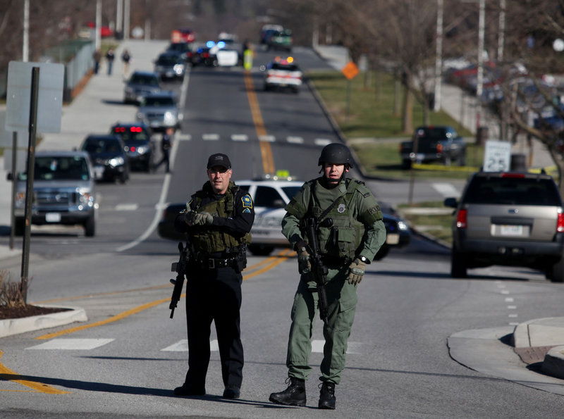 Police officers block a road on the Virginia Tech campus in Blacksburg, Va., after a gunman killed a police officer Thursday. The school said the officer pulled someone over for a traffic stop and was shot and killed.