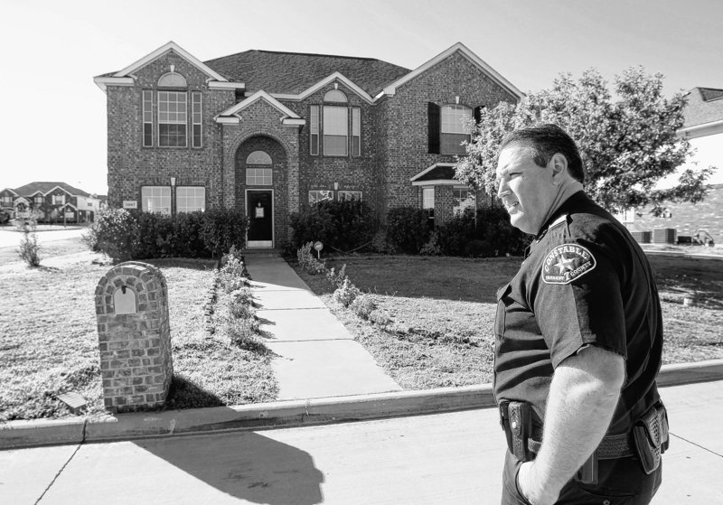 Constable Clint Burgess checks a house where squatters were evicted in Mansfield, Texas, late last month. Properties vulnerable to squatters include those whose owners died.