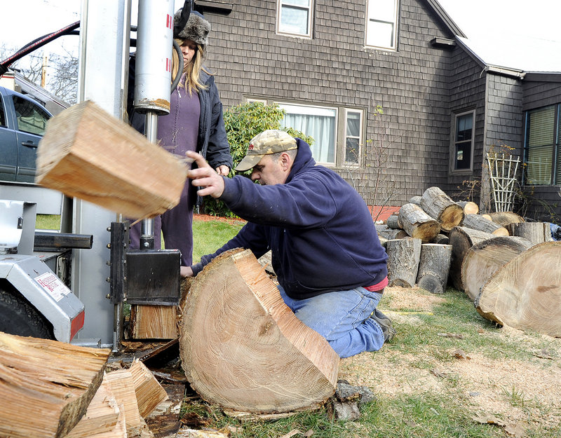 Kristen and Eric Flink split large pieces of red oak for firewood that their mother can use for the winter on Preble Street in South Portland on Friday.