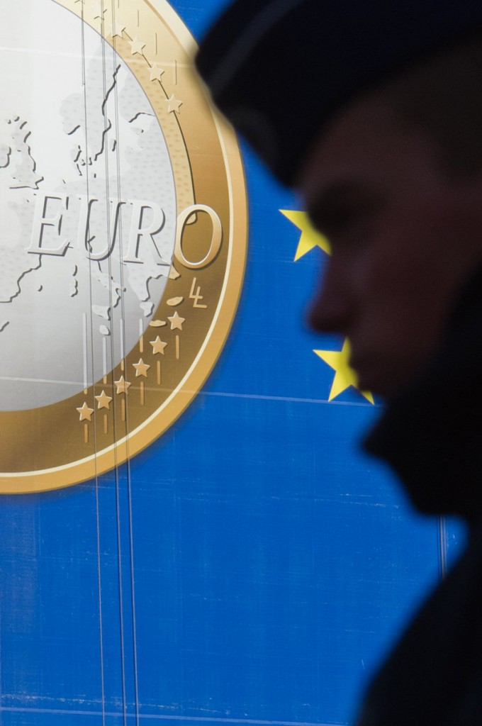 A man walks by a euro banner outside the EU summit in Brussels on Friday. A treaty to save the euro will include the 17 eurozone states plus as many as nine other countries.