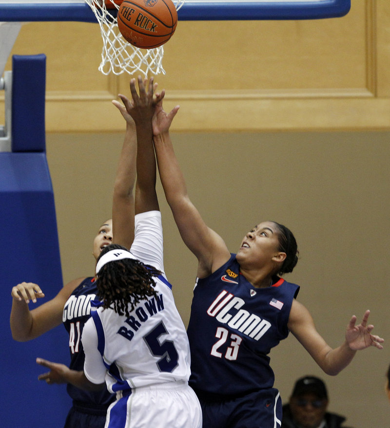 Kiah Stokes, left, and Kaleena Mosqueda-Lewis team up to block a shot by Seton Hall's Alexis Brown during Connecticut's 70-37 win Friday night.