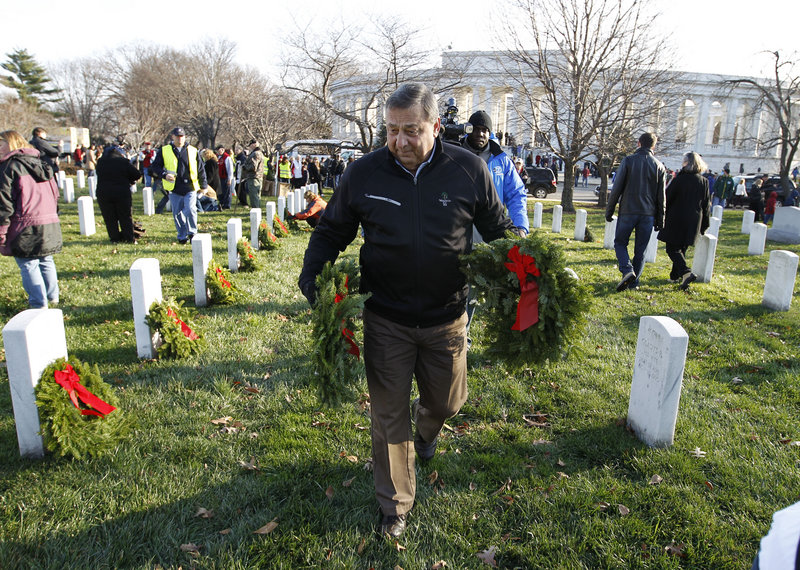 Maine Gov. Paul LePage prepares to place holiday wreaths at the grave of a fallen service member at Arlington National Cemetery during Wreaths Across America Day on Saturday.