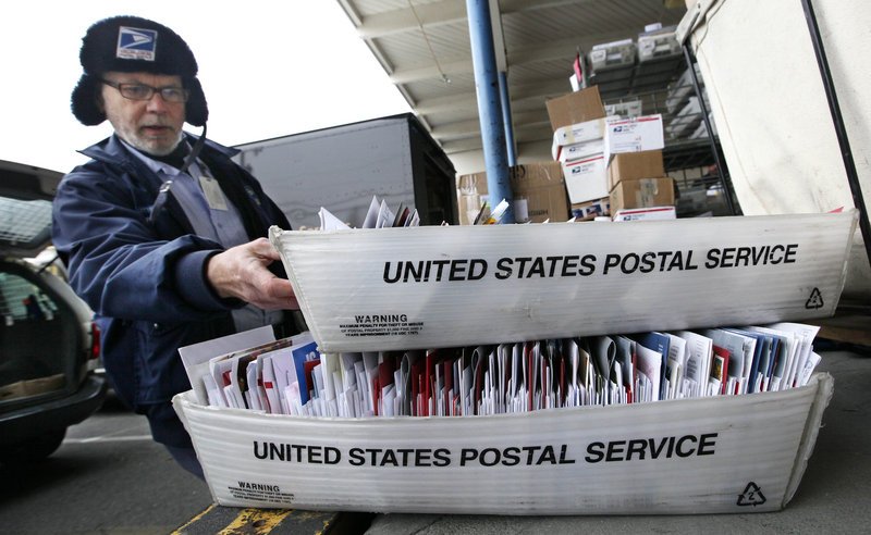 Letter carrier Sean Bailey loads mail into his van for delivery last week in Seattle. The U.S. Postal Service faces battles as it attempts to close 252 facilities and cut 28,000 jobs.