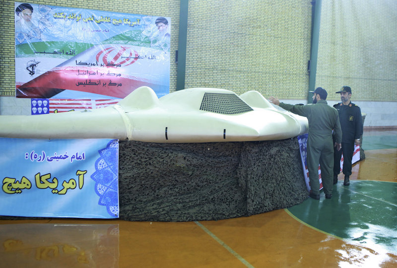 This photo, released Thursday by the Iranian Revolutionary Guards, claims to show the U.S. drone that Tehran says it downed last week. Gen. Amir Ali Hajizadeh, right, chief of the Guards' aerospace division, listens to an unidentified colonel.