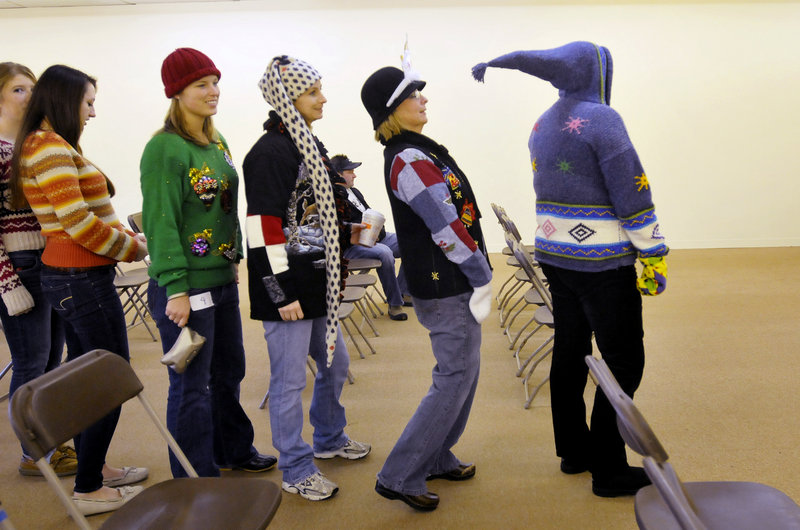 Roxanne Bennett of Kennebunk leans back to avoid getting poked by Brenda Mannino's pointy hooded sweater as contestants in the Ugly Holiday Sweater Contest line up for the judges at the Wells Corner Shopping Center on Sunday. Behind Bennett are her daughters Joy and Brittney, followed by Courtney Goodwin and Marie Lawton of Chelmsford, Mass.