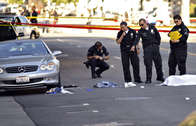 Investigators examine the scene of a fatal shooting in Hollywood on Friday. A man who fired at cars was shot to death by police after wounding a driver. The driver died Monday.