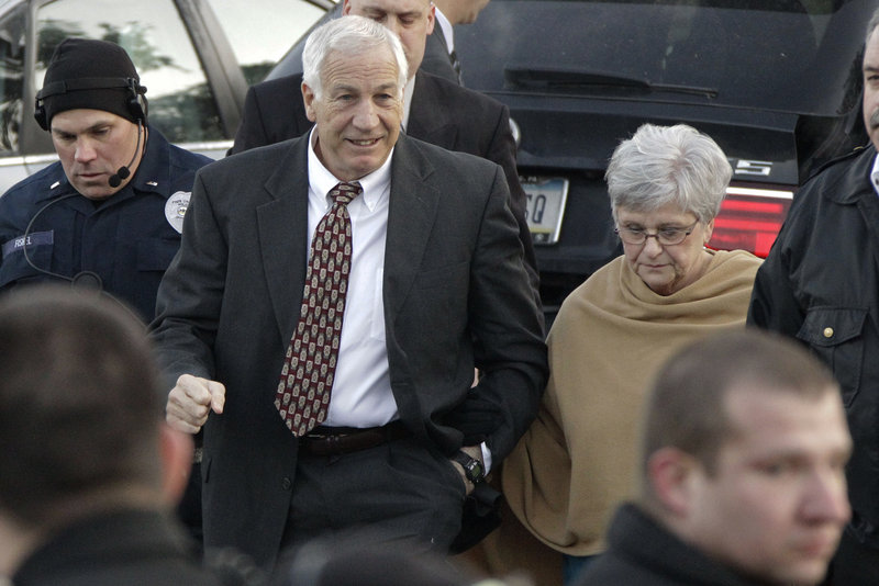 Jerry Sandusky, center, and his wife, Dottie, arrive Tuesday at the Centre County Courthouse in Bellefonte, Pa., where he pleaded not guilty to charges of sexually abusing 10 boys.