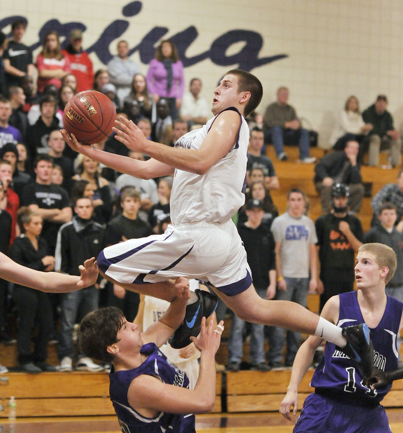 Jon Amabile, who scored 15 of his game-high 20 points for Deering in the first half Tuesday night, soars over Troy Pappas of Marshwood for a layup. Deering, down 30-25 at halftime, earned a 67-64 victory.