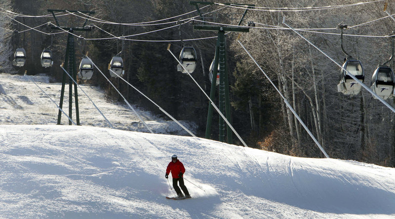 A lone skier uses an open trail at Loon Mountain ski area in Lincoln, N.H., on Monday while empty gondolas remain parked above.