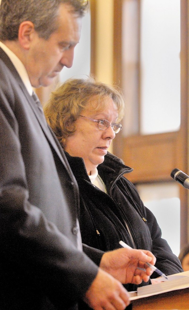 Bettysue Higgins stands Wednesday with her attorney Ronald Bourget in Kennebec County Superior Court where she pleaded guilty to embezzling $166,000 from the Maine Trial Lawyers Association.