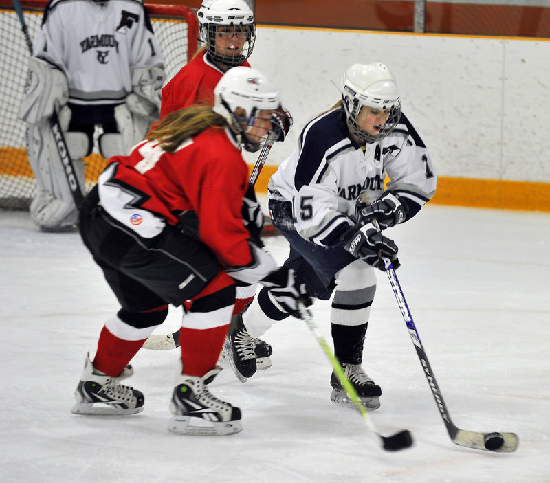 Caelainn Costello of Yarmouth-Freeport clears the puck while skating past Kayla Royer of Leavitt-Edward Little during the first period.