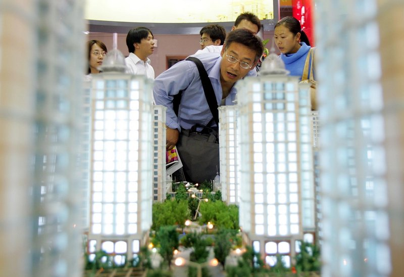 A man checks out a model of a planned housing complex at a real estate fair in Beijing. With average prices in the Shanghai area down about 40 percent from their peak in mid-2009, real estate buyers are more cautious.