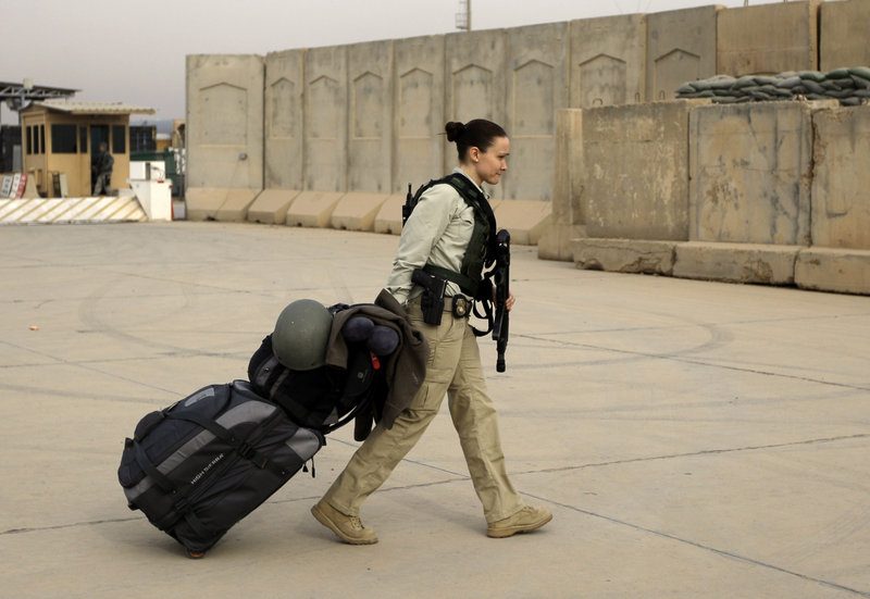 A security contractor begins her journey home after ceremonies Thursday marking the end of U.S. military mission in Iraq.