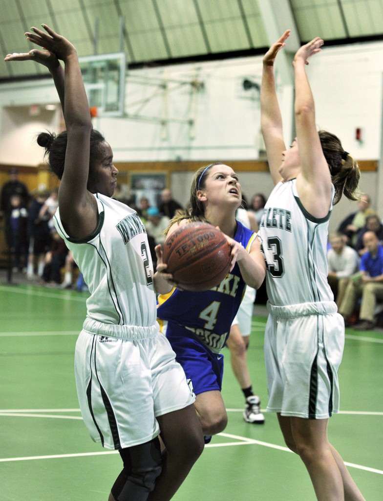 Sydney Hancock of Lake Region splits the defense, looking for room between Rhiannan Jackson, left, and Leigh Fernandez of Waynflete during their Western Maine Conference game Thursday. Lake Region won, 45-36.