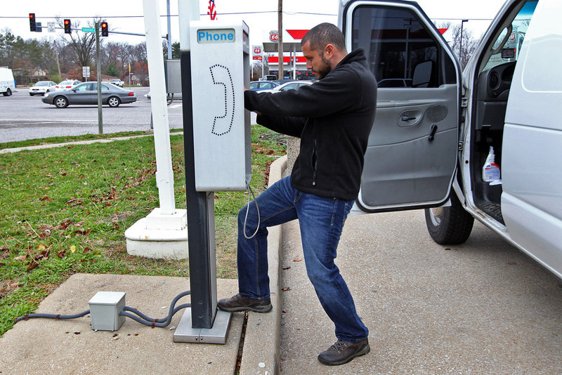 Joe Nesselhauf checks the operation on a pay phone in Mehlville, Mo., that is part of the business started by his grandfather. With the proliferation of cellphones, the pay phone business is dying out.