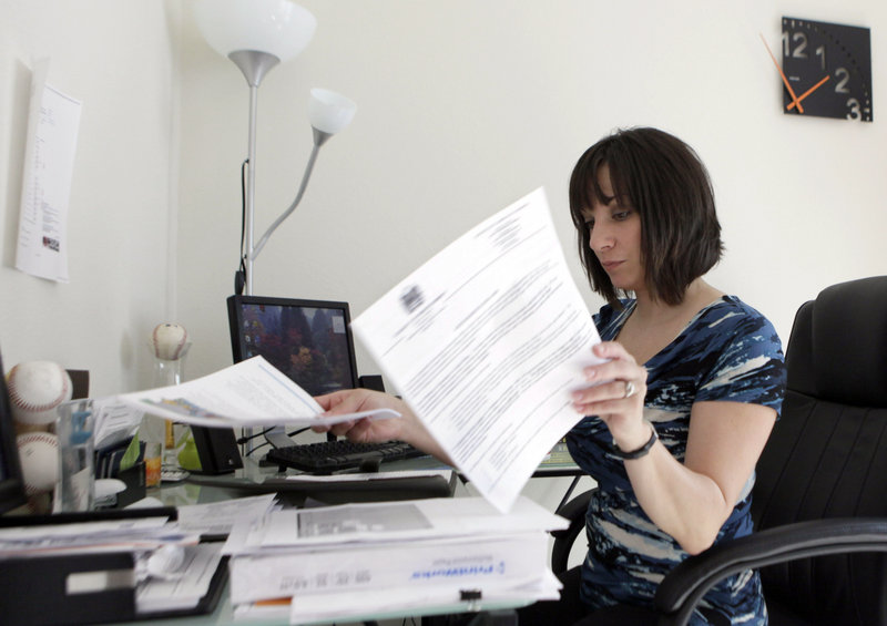 Gina Marie Haynes looks over documents before a job interview in Frisco, Texas. She has spent hours calling background check companies to get her record corrected after an outdated fraud charge, arising from a dispute over a car purchase, cost her a job.