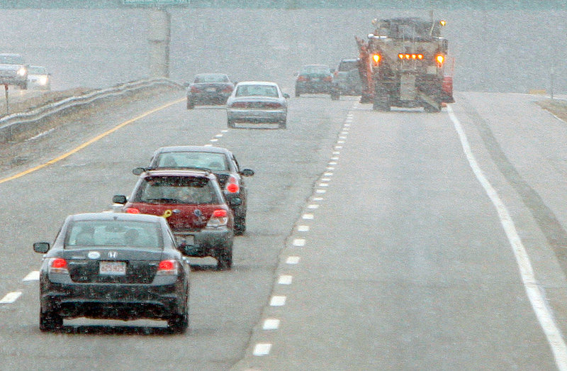 A plow truck patrols the northbound lane of the Maine Turnpike in Biddeford during a heavy snow squall Saturday. Snow and freezing temperatures caused numerous fender benders.