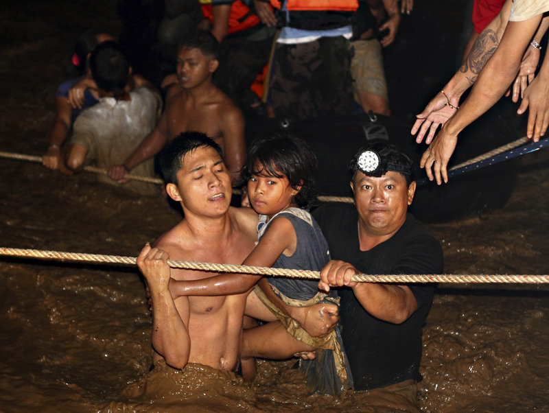 Residents are rescued by volunteers following a flash flood that inundated Cagayan de Oro city, Philippines, on Saturday.