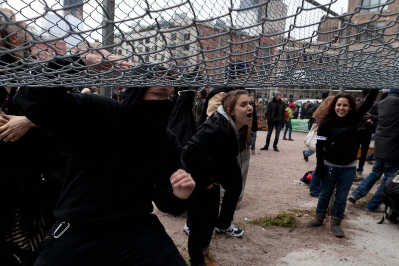Occupy Wall Street protesters lift a fence as they attempt to move onto land owned by the Episcopal Church in New York. A church official said that the lot would not be conducive to hosting the protesters.
