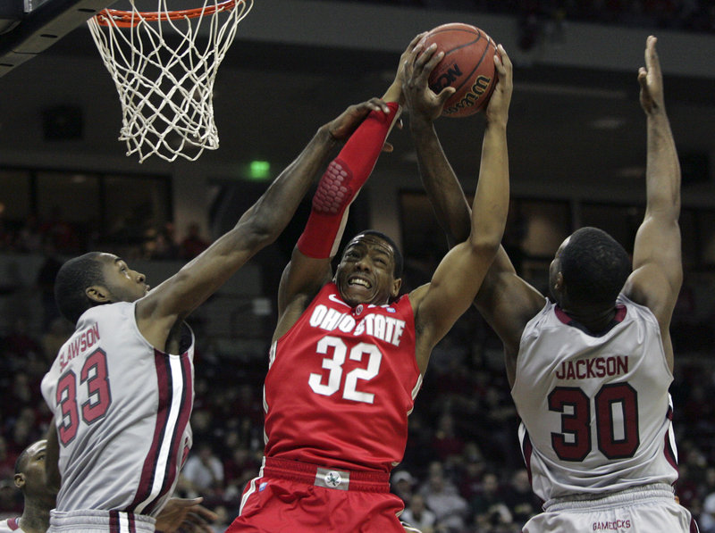 Lenzelle Smith of Ohio State grabs a rebound between South Carolina's R.J. Slawson, left, and Lakeem Jackson during the Buckeyes' 74-66 win Saturday in Columbia, S.C.