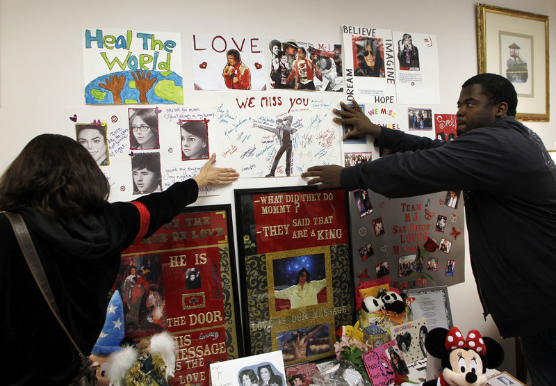 Michael Jackson fans Kim Lemieux, left, and Michael Craig hang a poster at a memorial to Jackson, during a private preview Dec. 11 at Julien's Auctions in Beverly Hills, Calif., of the contents of the home where the singer and his children lived at the time of his death.