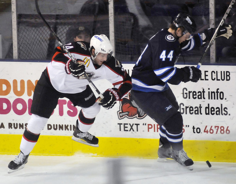 Arturs Kulda of the St. John's IceCaps tries to shield the puck from Portland's Brett Hextall during Sunday's game at the Cumberland County Civic Center.