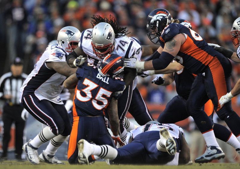 Kyle Love, 74, slams Denver Broncos running back Lance Ball in Sunday's game at Denver. The Patriots' defense allowed 167 rushing yards in the first quarter before regrouping in a 41-23 win over the Broncos.