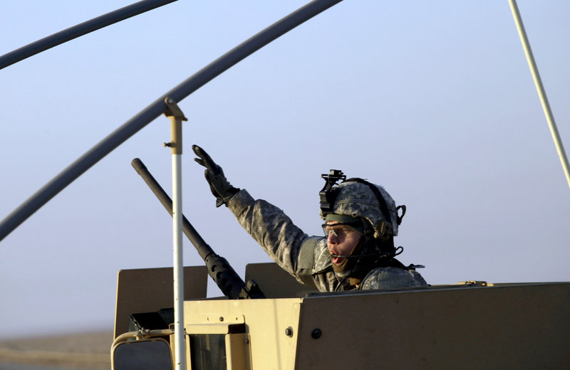 A soldier gestures from the gun turret of the last vehicle in a convoy of the U.S. Army's 3rd Brigade, 1st Cavalry Division, as it crosses the border from Iraq into Kuwait on Sunday. The brigade's special troops battalion were the last American soldiers to leave Iraq.