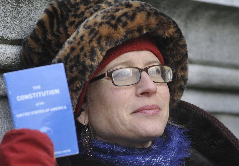 Heather Curtis, a plaintiff in the Occupy Maine lawsuit filed Monday against the city of Portland, holds a U.S. Constitution booklet outside Superior Court.