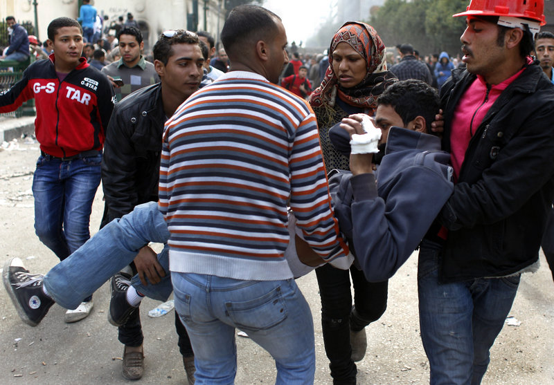 Egyptian demonstrators evacuate an injured fellow protester during clashes with army soldiers Sunday in Cairo.