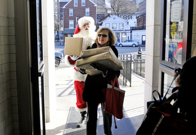 "Santa Claus helps Arlene Schwind at the Forest Avenue post office Tuesday. Santa is played by David Knight, postmaster for the town of Denmark who volunteered on his day off to greet customers. ""Maybe I'm old-fashioned, but I feel (the post office) is a service, not a business,"" he said."