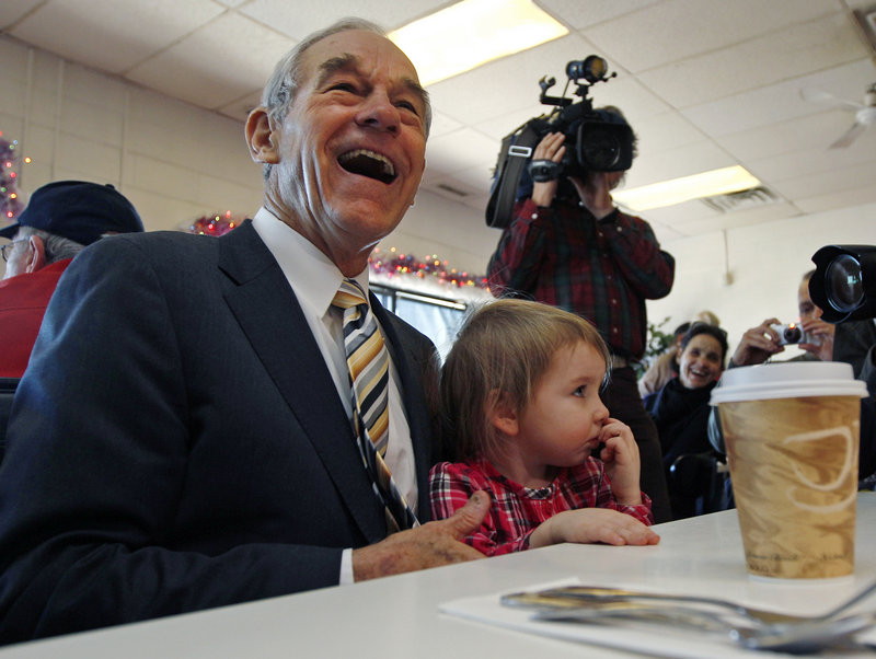 Rep. Ron Paul, R-Texas, sits with Elizabeth Rose Chamberlain, 3, of Epping, N.H., while campaigning at the Early Bird Cafe in Plaistow on Tuesday. The presidential candidate's fiscal conservatism has gained him supporters.