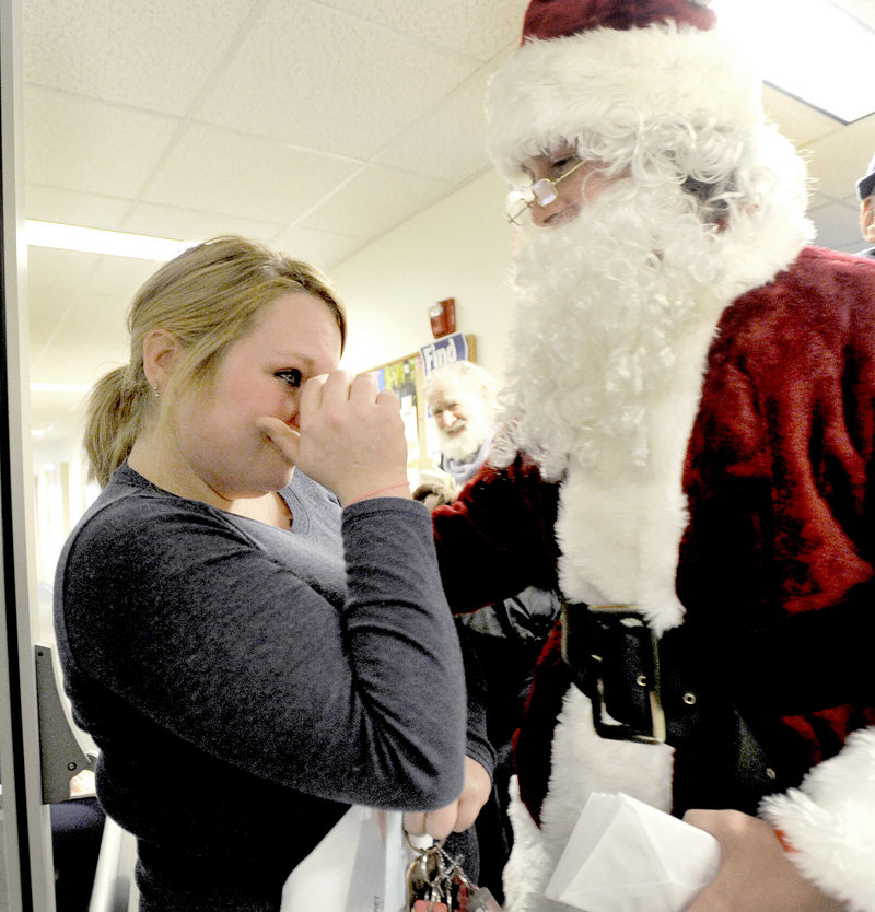 Missy Knight from Lisbon Falls wipes away a tear after receiving a $100 bill from Secret Santa's assistant at the Mid Coast Hunger Prevention Program in Brunswick on Wednesday.