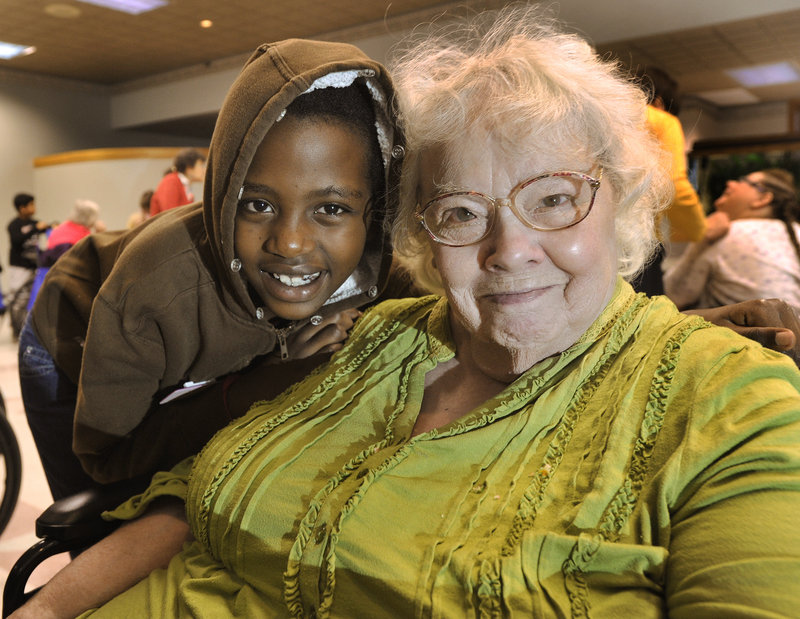 Hall Elementary School third-grader Lydia Rumyambo shares a goodbye hug with her friend Margaret Marino after a Christmas party at the Baron Center in Portland. A reader says photos like this one by Press Herald staffer John Ewing made the holidays brighter for her.