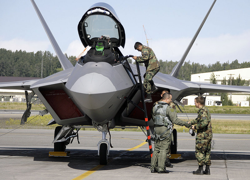 Lt. Col. Mike Shower, commander of the 90th Fighter Squadron, center, is greeted by crew chiefs after landing an F-22 fighter jet during an August 2007 arrival ceremony at Elmendorf Air Force Base in Anchorage, Alaska.