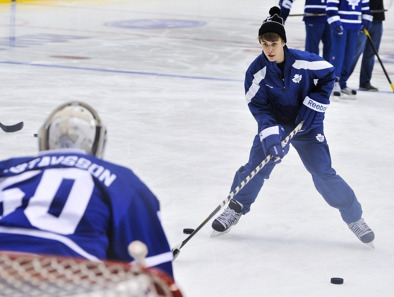 Singer Justin Bieber tries to get a shot past the Maple Leafs' goalie Wednesday in Toronto.