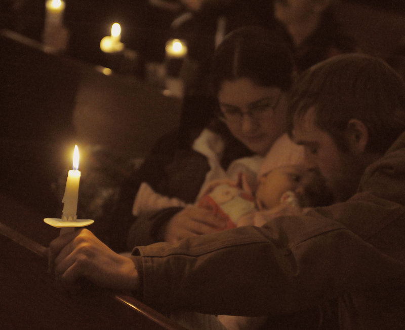 Ken Brown and Hannah Letourneau hold their daughter Mackenzie Brown as prayers are offered Wednesday night during a vigil for Ayla Reynolds at a Waterville church.