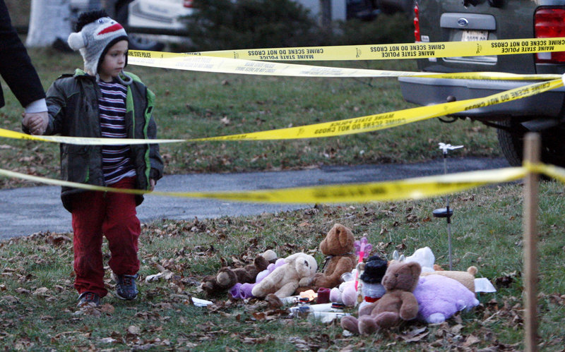 Isaiah Vear, 5, of Waterville walks away from a memorial of stuffed toys after he placed a toy for missing 20-month-old Ayla Reynolds outside her home Thursday. People gathered at a Waterville church Wednesday night for a candlelight vigil.
